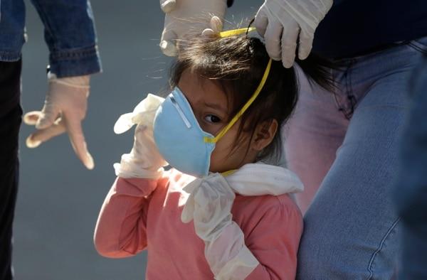 Antes de que los menores salgan a la calle con mascarillas u otro tipo de equipo de protección estos deben aprender cómo usarlos. Además, deberán adaptarse al tamaño de su cara. Fotografía con fines ilustrativos: AP Photo/Martin Mejia