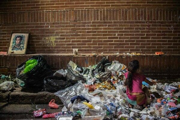 Una niña busca comida entre la basura en las calles de Caracas, Venezuela.