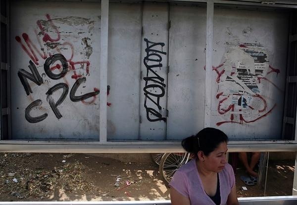 En esta fotografía del 2008, una mujer aparece al lado de un grafiti contra los Consejos del Poder Ciudadano, aprobados ese año e incorporados ahora en la Constitución. La oposición califica esos órganos como instrumento político de control ciudadano. Estos órganos deben dar el aval para que un ciudadano trabaje en el Gobierno.   ARCHIVO.