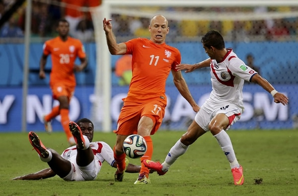 Arjen Robben deja en el camino a Joel Campbell y trata de sacar a Gamboa, con quien se ha visto en varias ocasiones en la primera parte.   EFE