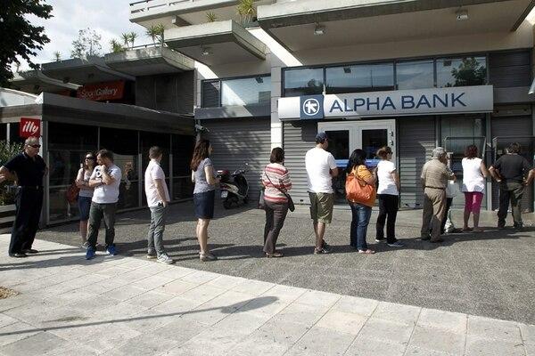 Varias personas hicieron fila ayer para retirar dinero de los cajeros automáticos en Atenas, luego de que el viernes el primer ministro griego llamara a un referendo sobre el acuerdo de la deuda griega. | EFE