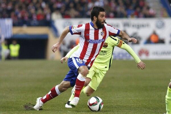 El centrocampista turco del Atlético de Madrid, Arda Turan (izquierda), conduce el balón ante el jugador del F. C. Barcelona, Andrés Iniesta.