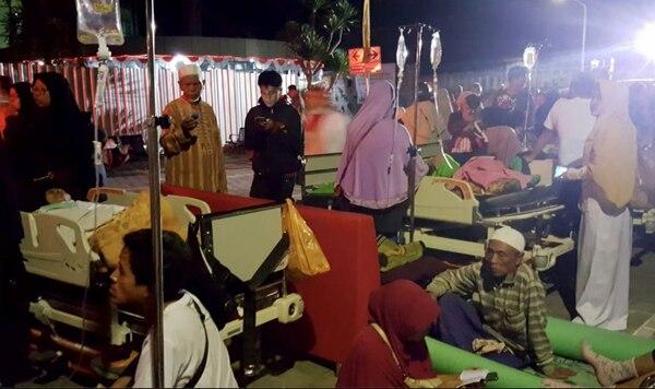 Pacientes y familiares esperan afuera del hospital tras ser evacuados después de que un terremoto sacudiera la isla indonesia de Lombok, en Mataram, el 5 de agosto de 2018. AFP