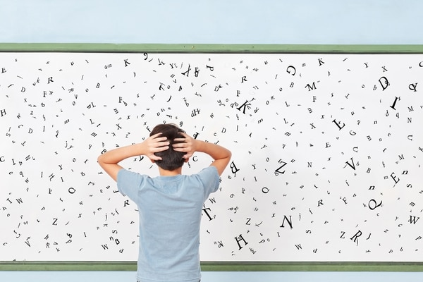 Dislexia Child with dyslexia is standing in front of a blackboard with many letters at school