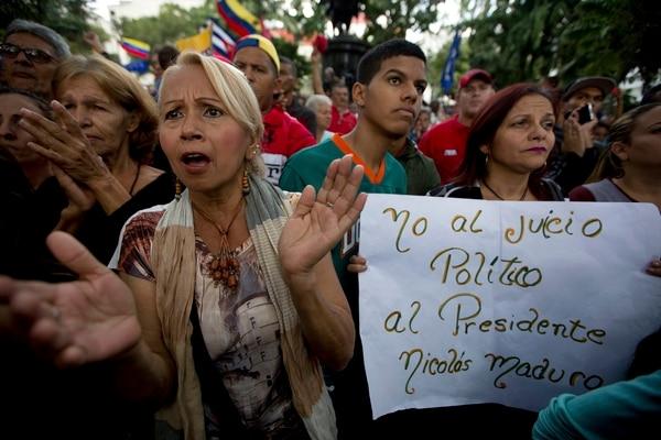 Seguidores del gobierno del presidente Nicolás Maduro rechazaron el martes, en Caracas, un posible juicio político, como lo pretende la oposición.