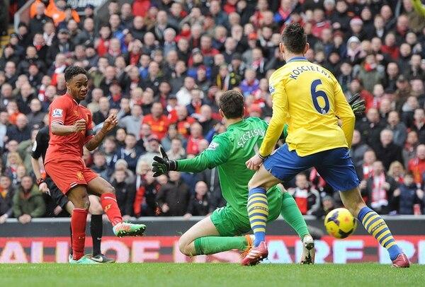 Raheem Sterling, de Liverpool, marca ante el portero Wojciech Szczesny y Laurent Koscielny, de Arsenal.   EFE