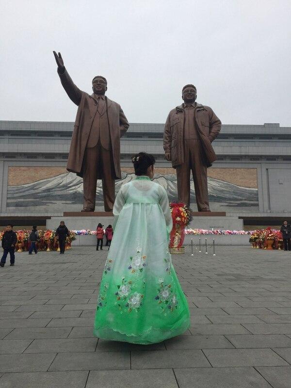 Una mujer, vestida con traje tradicional, presenta sus respetos a las estatuas de los líderes de Corea del Norte: Kim Il Sung, Izquierda, y Kim Jong Il.