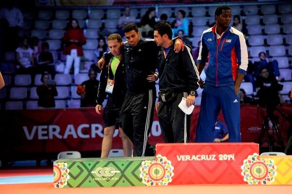 El taekwondista tico Kristopher Moitland, lesionado en la final ante el cubano Robelis Despaigne (der.), tuvo que ser llevado al podio por dos colegas (no identificados) para recibir su presea de plata. | MELISSA FERNÁNDEZ