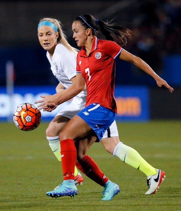 La defensa estadounidense Julie Johnston busca quitarle el balón a la delantera costarricense Melissa Herrera (7).   AP