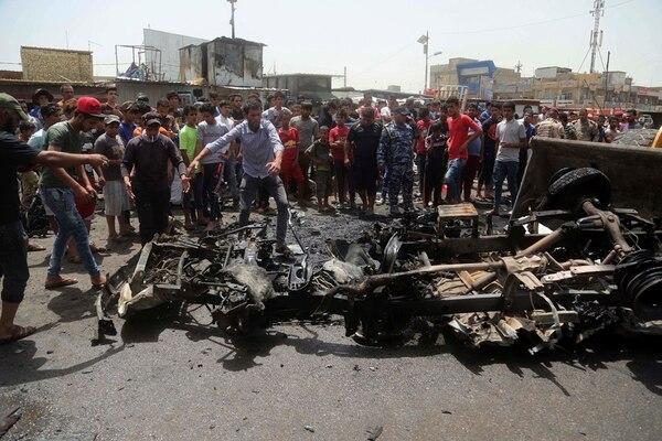 Ciudadanos revisaban la escena después de la explosión de un coche bomba en un mercado al aire libre, lleno de gente, en Ciudad Sadr. | AP