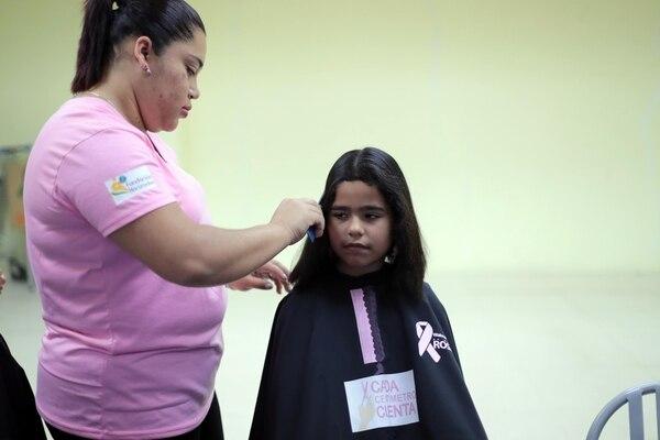 Grecherll Rojas, de ocho años, es vecina de Grecia. Ella llegó hasta el Walmart de San Sebastián en San José para donar su cabello. María Fernanda Aguirre cortó su cabello. Foto: Alonso Tenorio