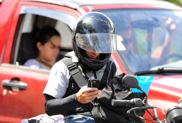 Un motociclista atiende su teléfono celular en la vía principal de La Uruca.