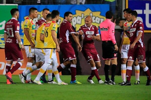 Jugadores de Saprissa y Herediano reclaman a Wálter Quesada durante el partido.
