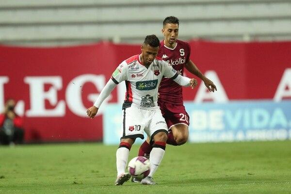 Alex López golpea un balón ante la mirada de Mariano Torres en la final de ida del Clausura 2020. Fotografía José Cordero