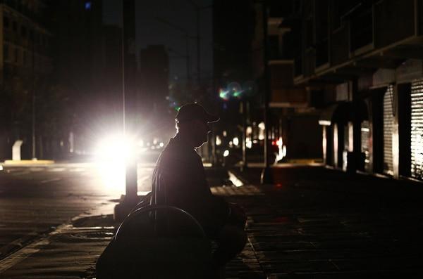 Un hombre en silla de ruedas en las calles de Caracas, durante el apagón.