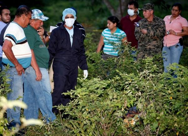 Personal forense, familiares y agentes policiales en el sitio donde el lunes se encontró el cadáver del periodista Herlyn Espinal, en las afueras de San Pedro Sula.