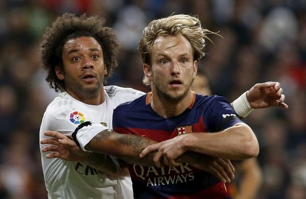 Marcelo Vieira intenta sujetar al centrocampista del FC Barcelona Ivan Rakitic durante el clásico que se jugó el sábado en el estadio Santiago Bernabéu.