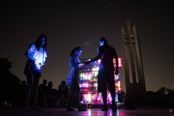 TOPSHOT - A vendor sells light-up yoys in front of the Quezon Memorial Shrine after the switching off lights for the Earth Hour environmental campaign in Manila on March 24, 2018. / AFP PHOTO / NOEL CELIS