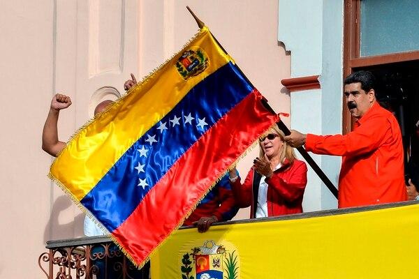 El presidente Nicolás Maduro agitaba una bandera mientras les hablaba a sus simpatizantes, el miércoles 23 de enero del 2019, desde un balcón del palacio de Miraflores, en Caracas.
