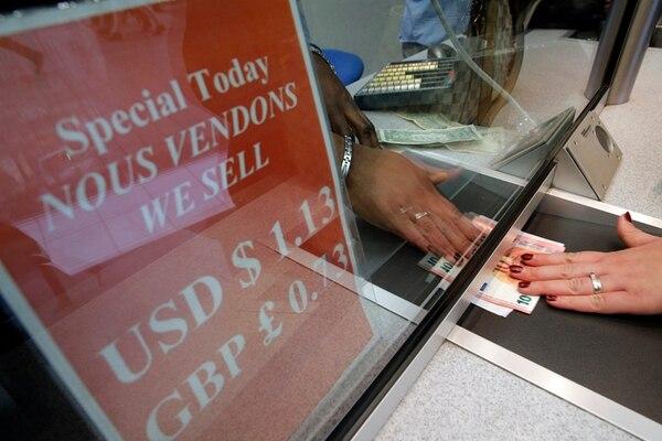 Una mujer recurre a una oficina de cambio de moneda en los Campos Elíseos, en París. El euro se hundió el lunes ante nuevas dudas sobre la permanencia de Grecia en la llamada zona euro. | AP