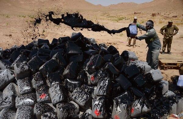 Policías afganos arrojaban combustible sobre envases llenos de ácido acético que fueron confiscados en las afueras de la ciudad de Herat.