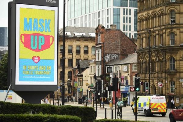 Un mensaje en una pizarra electrónica instaba a la gente a usar mascarilla cuando realiza compras y en el transporte público, este viernes 31 de julio del 2020 en Mánchester, Inglaterra. AFP