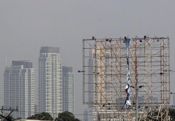 Un trabajador retira un cartel publicitario en preparación a la llegada del tifón