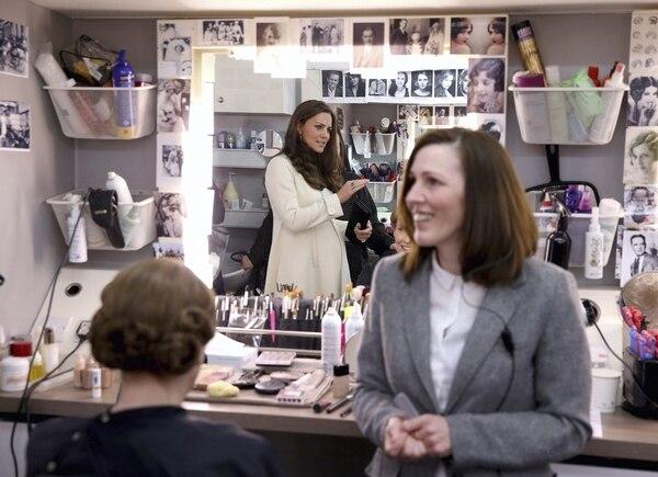 La duquesa de Cambridge, Catalina, conversa con la maquilladora y peluquera Nic Collins (der.) mientras preparan a la actriz Phyliss Logan (izq.) durante su visita a los estudios donde se filma la exitosa serie 'Downton Abbey', en Ealing, Londres.