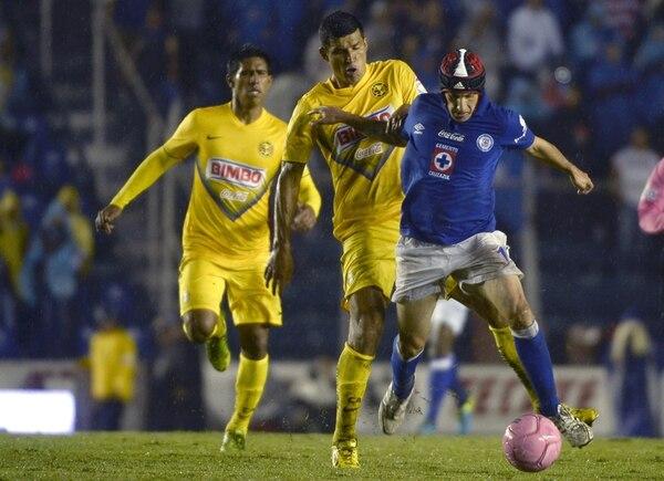 Franciso Rodríguez (centro) presiona por detrás al habilidoso jugador del Cruz Azul Christian Giménez, en una edición más del clásico joven. | AFP