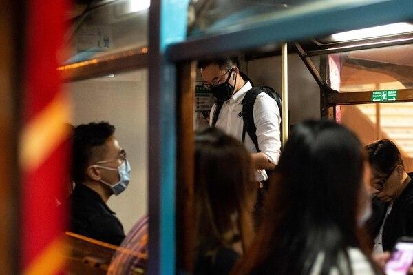 Los pasajeros usan máscaras protectoras mientras viajan en el tranvía durante la hora pico de la noche en Hong Kong el 23 de enero del 2020. Hong Kong ha convertido dos campamentos de vacaciones, incluido un antiguo cuartel militar, en zonas de cuarentena para las personas que pueden haber estado en contacto con portadores del virus. Foto: AFP