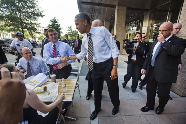 El presidente Barack Obama (centro), saludó ayer mientras caminaba de la Casa Blanca a un restaurante en la avenida Pensilvania, en Washington. | EFE