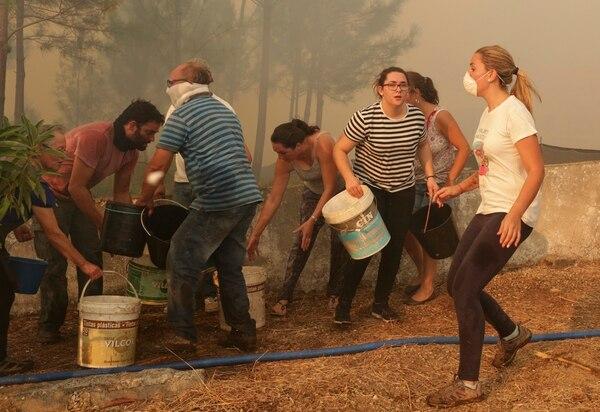 Aldeanos se apresuran con baldes de agua para combatir las llamas que llegan cerca de sus casas en el pueblo de Chao de Codes, cerca de Macao, en el centro de Portugal, el miércoles 16 de agosto.