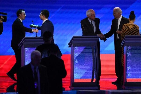 El exvicepresidente Joe Biden (derecha) y el senador Bernie Sanders se saludaro, en tant que el exalcalde Pete Buttigieg (segundo, izquierda) se disponía a abrazar a su esposo, Chasten, al terminar el debate demócrata en Manchester, Nuevo Hampshire.