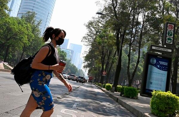 Una mujer usa una mascarilla mientras camina por una céntrica calle de la Ciudad de México el 14 de mayo de 2019. Foto: AFP
