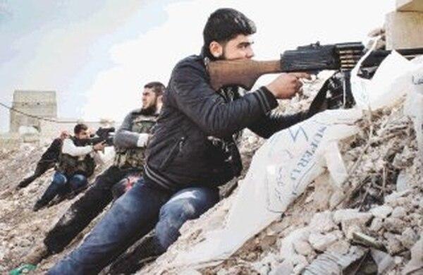 Rebeldes sirios apostados el sábado en posiciones en las afueras de la ciudad de Maraat al-Numan, provincia de Idlib. | AP.