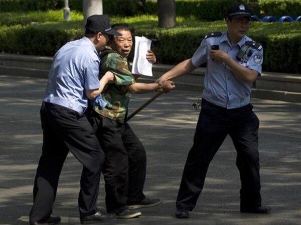 Dos policías detuvieron el 8 de mayo del 2012 a este hombre que intentaba llamar la atención afuera de un hospital en Pekín, donde se encontraba el activista ciego Chen Guangcheng. | ARCHIVO