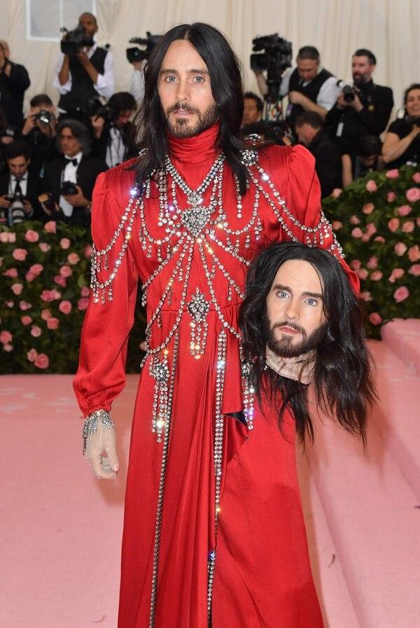 Jared Leto optó por un vestido rojo con adornos plateados y lució su larga cabellera suelta. El cantante utilizó como terrorífico accesorio un maniquí con su propio rostro. Foto: AFP)