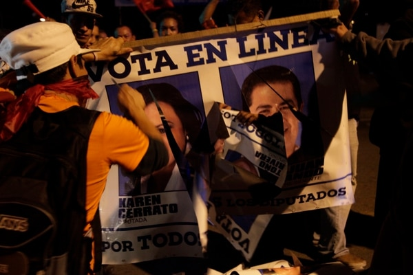 Anti-government demonstrators shatter a campaign poster of the National Party with a portrait of Honduran President Juan Orlando Hernandez during a march at the Morazan street in Tegucigalpa, Honduras, Friday, Dec. 8, 2017. International observers urged Honduras' opposition Friday to file a formal complaint about the country's troubled Nov. 26 election as the deadline fast approaches.(AP Photo/Fernando Antonio)