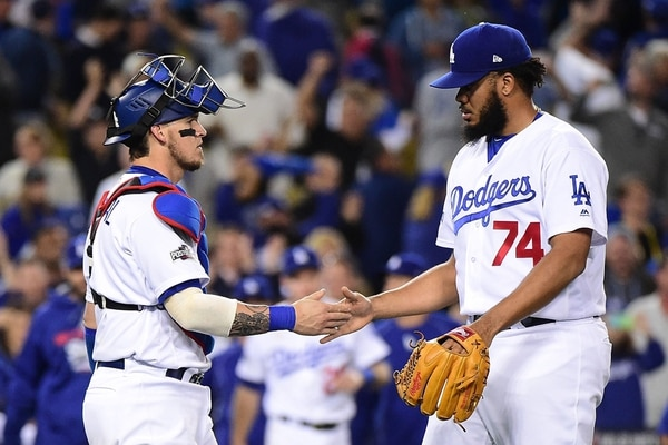 El receptor de los Dodgers de Los Ángeles, Yasmani Grandal (derecha), felicita al relevista Kenley Jansen por la victoria ante los Cachorros. | AFP