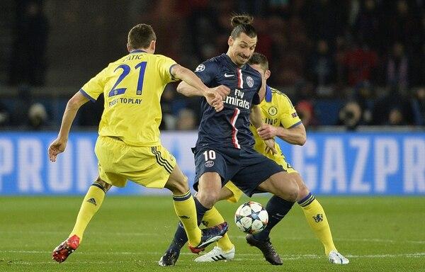 El delantero sueco del París Saint-Germain, Zlatan Ibrahimovic (centro), defiende el control del balón ante Gary Cahill y Nemanja Matic (izq) del Chelsea, durante los octavos de final de la Champions League.