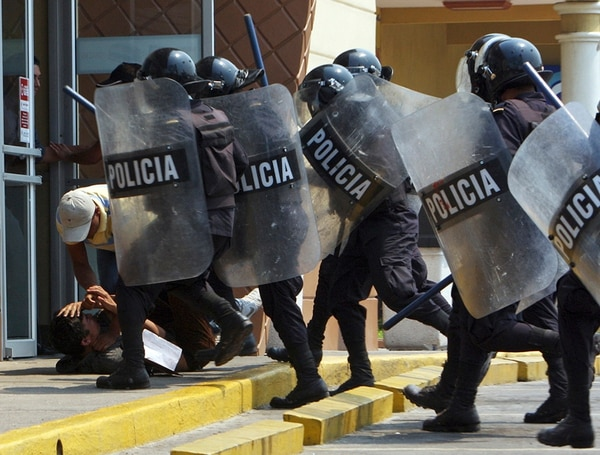 Agentes policiales hondureños frenan una protesta el 30 de marzo del 2011 en Tegucigalpa. Actualmente la Policía tiene en planillas unos 14.000 agentes, pero en las comisarías sólo se registran activos 9.500. | ARCHIVO / AP.