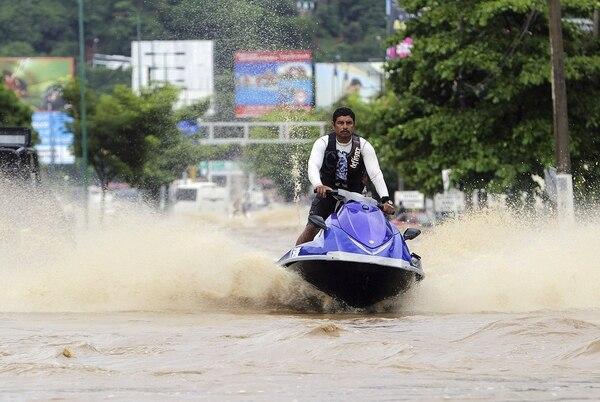 Un hombre monta una moto de agua en una calle inundada en Acapulco, estado de Guerrero, México, después de las fuertes lluvias que golpean la zona desde el fin de semana.