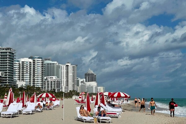 (FILES) In this file photo taken on December 20, 2020, people enjoy the beach in Miami, Florida, amid the Coronavirus pandemic. - The city of Miami, which is becoming a financial hub of the United States thanks to its subtropical climate and the absence of income taxes, is now aiming to attract the