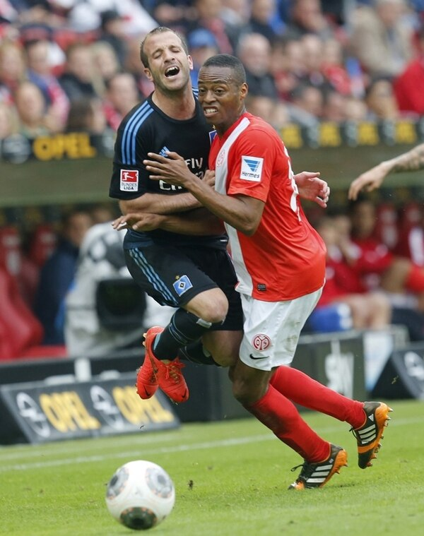 Júnior Díaz (der.) choca contra Rafael van der Vaart, del Hamburgo. | AP