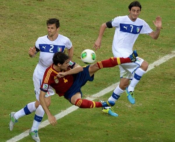 El mediocampista español Javi Martínez (4) cae entre la marca de los jugadores italianos Christian Maggio (2) y Alberto Aquilani. | AFP
