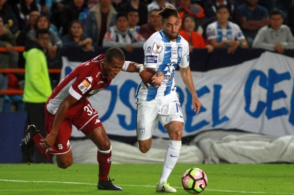 El defensor nacional Roy Miller intenta detener al uruguayo Jonathan Urretavicaya.