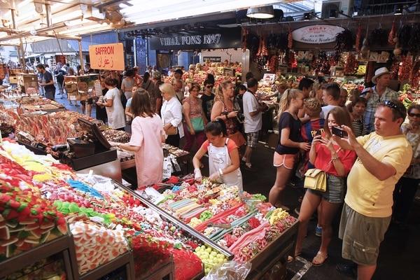 Turistas toman fotografías en el mercado La Boquería, en Barcelona. Los 27 millones de visitantes anuales que llegan a esa ciudad generan el 14% de la producción del municipio.