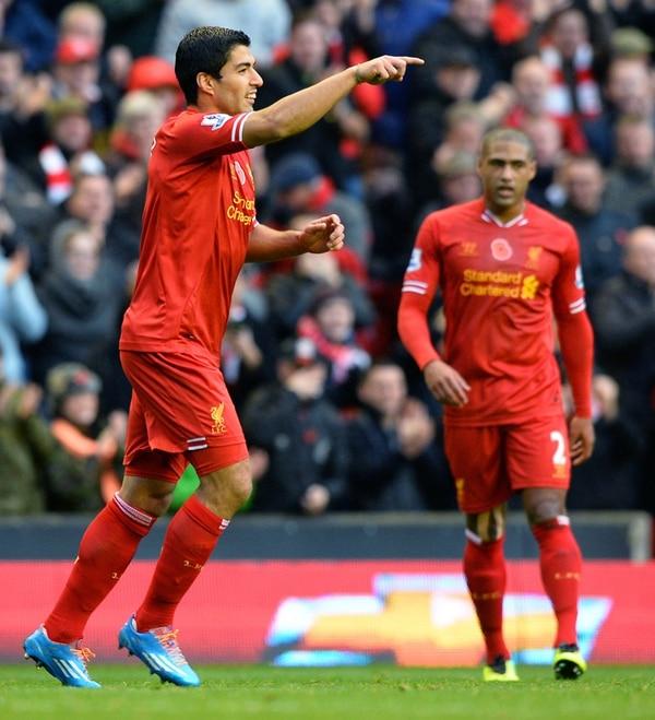El delantero uruguayo Luis Suárez (izquierda) celebra su segundo gol ante el Fulham, gracias a la asistencia que le dio Glen Johnson (al fondo).   AP
