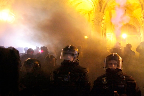 TOPSHOT - Riot police stand guard during a protest against the dubbed