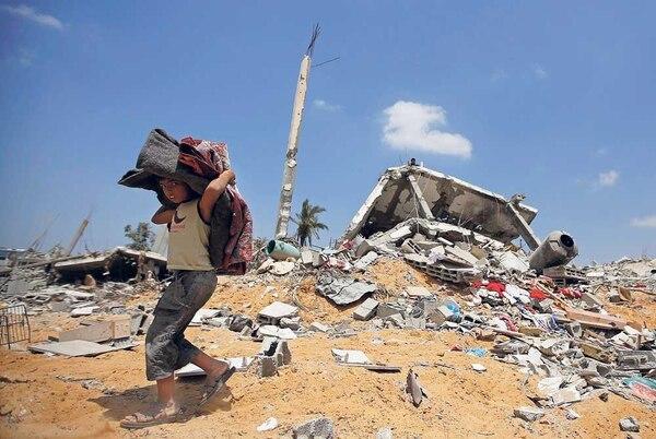 Un joven palestino carga con varias de sus pertenencias tras rescatarlas de su destruida vivienda en el barrio de Khoza, en el este de la ciuad de Janyunis, al sur de la franja de Gaza.